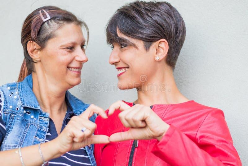 Pares lesbianos que forman forma del corazón con las manos fotografía de archivo