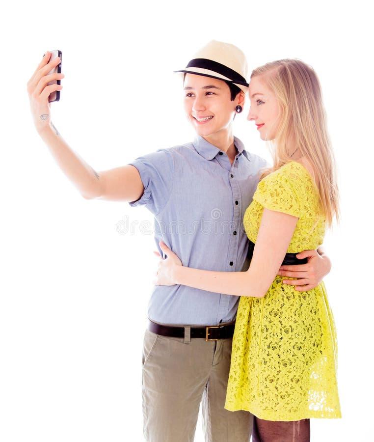 Pares lesbianos que toman la imagen de sí misma con un teléfono móvil fotografía de archivo libre de regalías