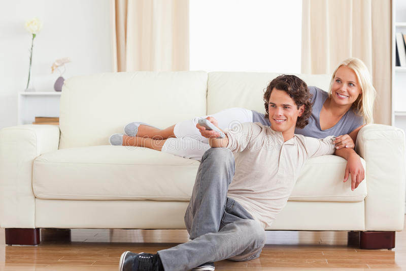 Pares lindos de risa que ven la TV imagen de archivo libre de regalías