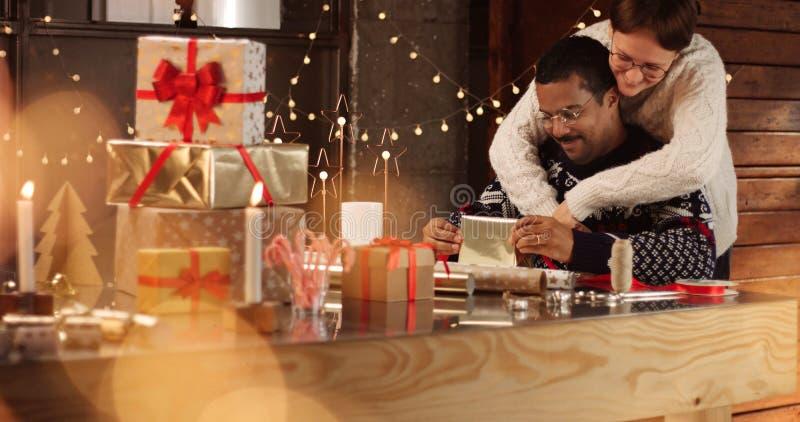 Pares lindos en los suéteres del invierno que envuelven regalos de Navidad fotos de archivo