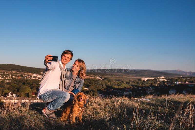 Pares lindos jovenes felices que hacen el selfie al aire libre fotos de archivo