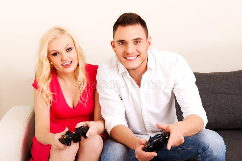 Pares lindos jovenes que juegan a los videojuegos imagenes de archivo