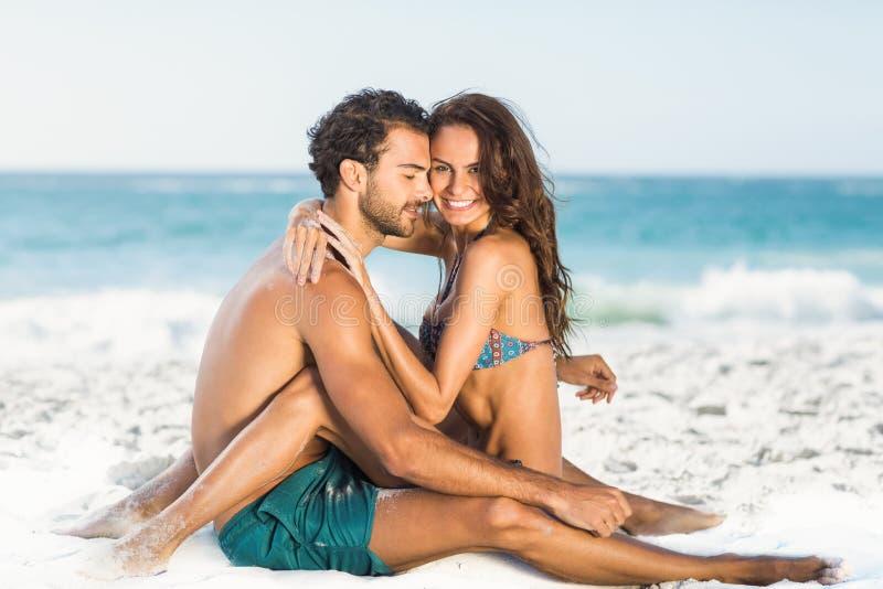 Pares lindos que abrazan sentarse en la playa imagenes de archivo