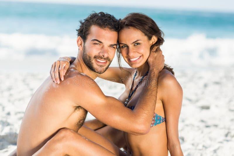 Pares lindos que abrazan sentarse en la playa imagen de archivo libre de regalías