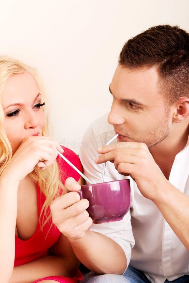 Pares lindos que beben a partir de una taza imagen de archivo