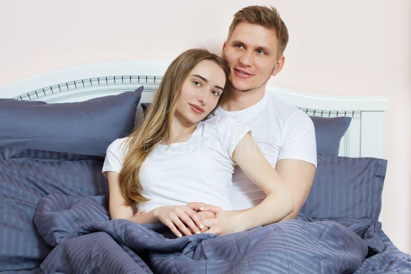 Pares lindos que se relajan en cama y concepto del abrazo, del amor y de las relaciones foto de archivo libre de regalías