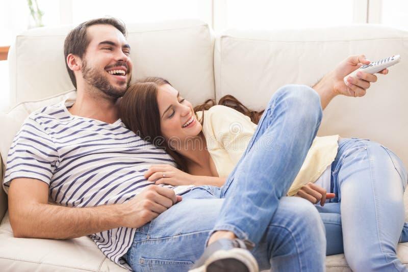 Pares lindos que se relajan en el sofá imagenes de archivo