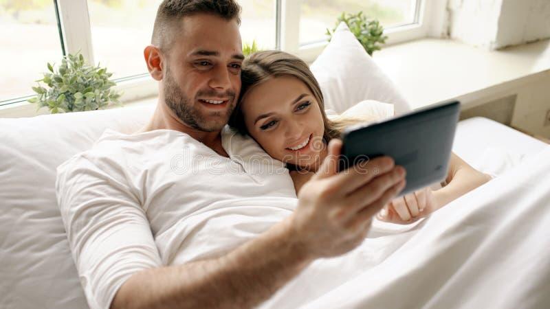 Pares lindos y cariñosos jovenes usando la tableta y mentira que habla en cama en el dormitorio en la mañana foto de archivo libre de regalías