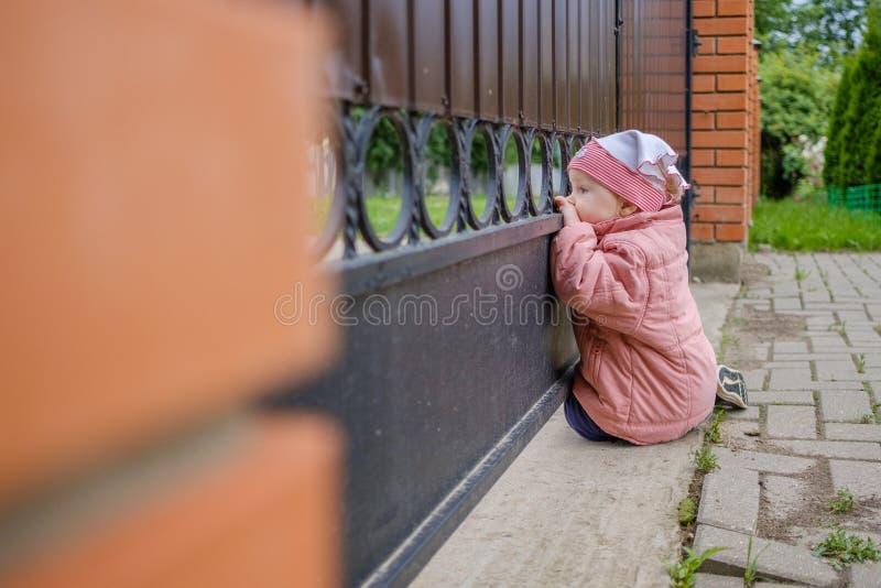 Pares louros pequenos de uma menina para fora através das barras da porta Um bebê curioso feliz está explorando o mundo com inter fotografia de stock royalty free
