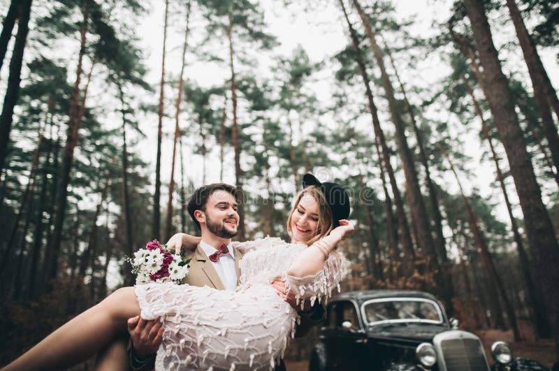 Pares loving à moda do casamento que beijam e que abraçam em uma floresta do pinho perto do carro retro fotos de stock