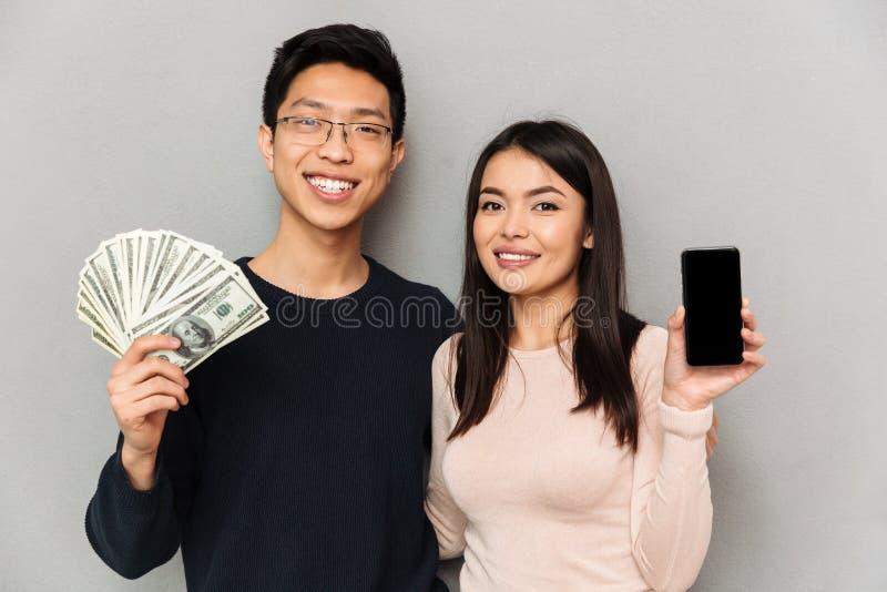 Pares loving asiáticos novos alegres que guardam o dinheiro e que mostram a exposição do telefone celular fotografia de stock