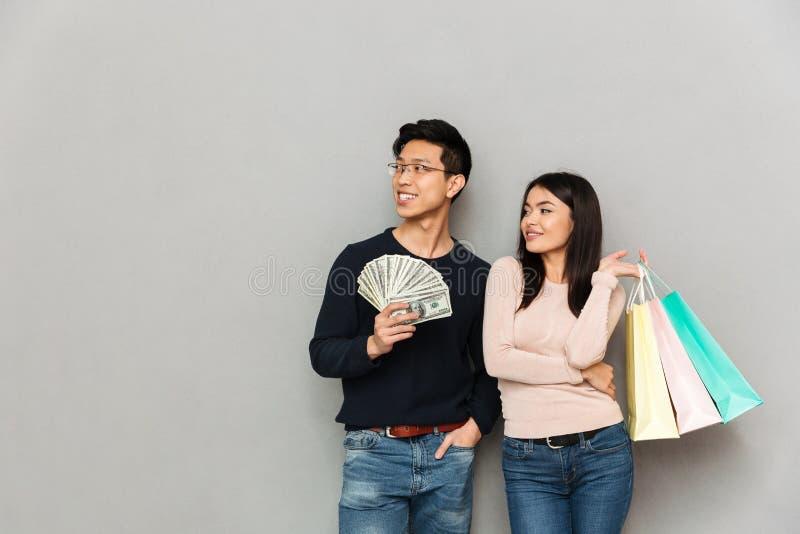 Pares loving asiáticos novos alegres que guardam o dinheiro e os sacos de compras Vista de lado fotografia de stock royalty free