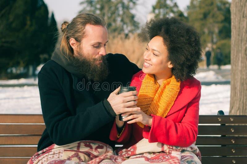 Pares loving com as bebidas quentes que sentam-se no banco no inverno fotografia de stock royalty free