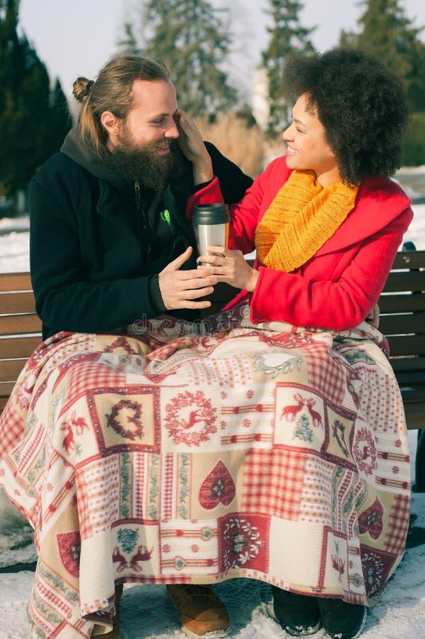 Pares loving com as bebidas quentes que sentam-se no banco no inverno imagens de stock