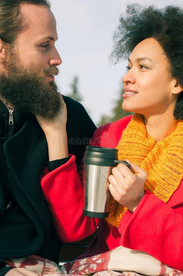 Pares loving com as bebidas quentes que sentam-se no banco no inverno imagens de stock royalty free