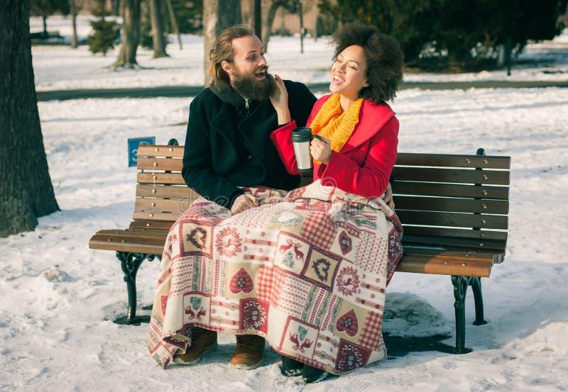 Pares loving com as bebidas quentes que sentam-se no banco no inverno fotos de stock