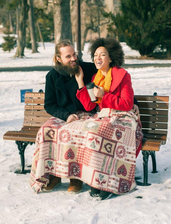 Pares loving com as bebidas quentes que sentam-se no banco no inverno foto de stock