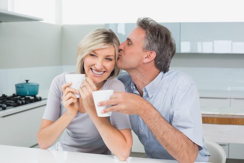Pares loving com os copos de café na cozinha foto de stock royalty free