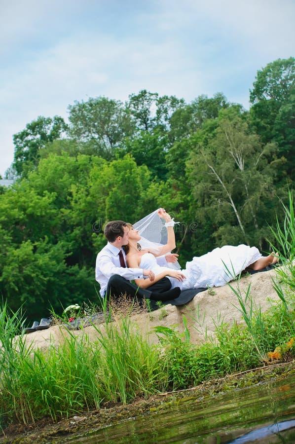 Pares loving do casamento que sentam-se na areia perto da água imagem de stock