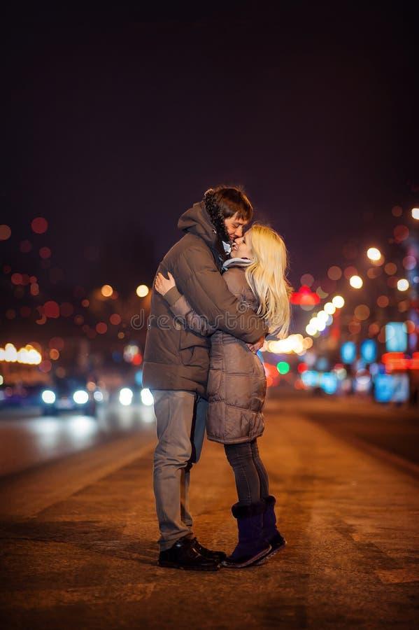 Pares loving em um fundo da cidade do inverno da noite fotografia de stock