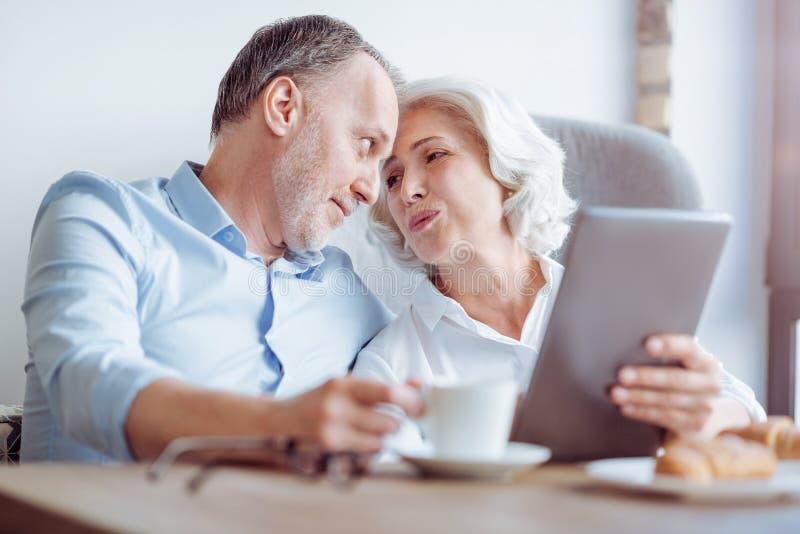 Pares loving envelhecidos agradáveis que sentam-se na tabela fotografia de stock