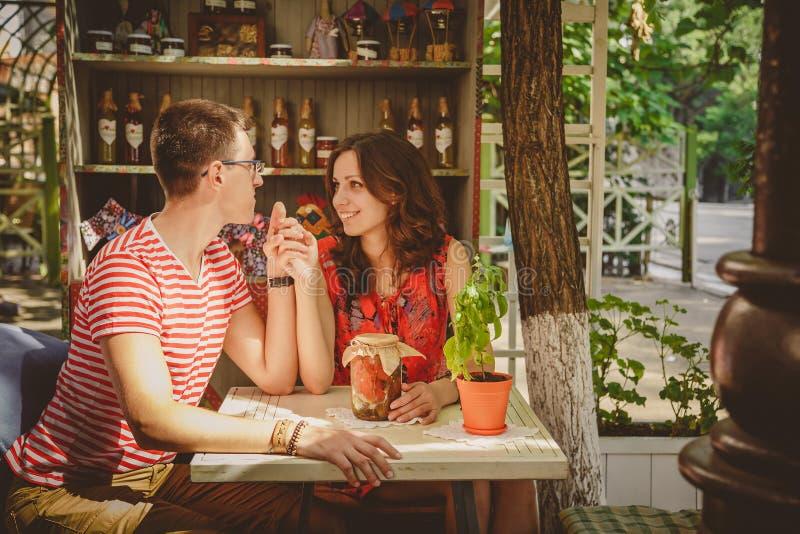 Pares loving felizes bonitos novos que sentam-se no café ao ar livre da rua que guarda as mãos que olham se Começo da história de imagem de stock