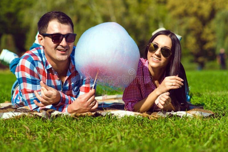 Pares loving felizes de sorriso dos jovens em camisas verificadas e nos óculos de sol que encontram-se no gramado verde e que com fotografia de stock royalty free
