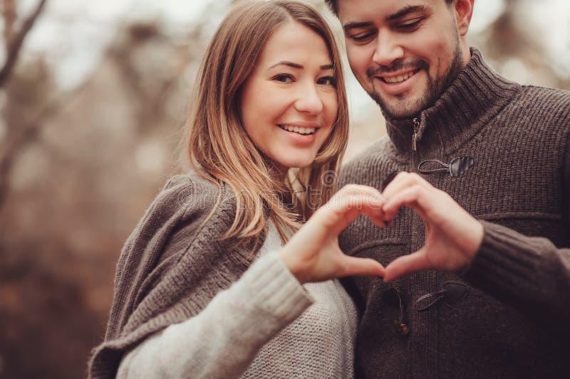 Pares loving felizes novos que mostram o coração para o dia de são valentim na caminhada exterior acolhedor na floresta imagem de stock