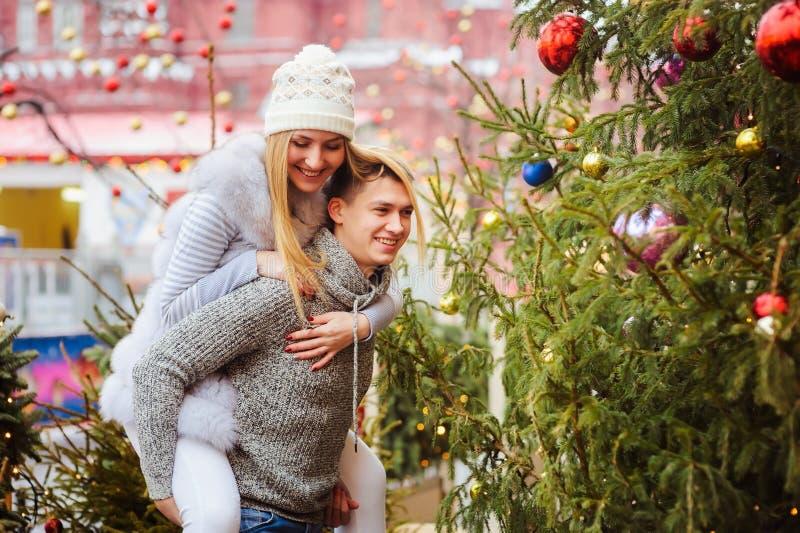 Pares loving felizes que apreciam os feriados do Natal ou do ano novo exteriores em ruas da cidade imagem de stock