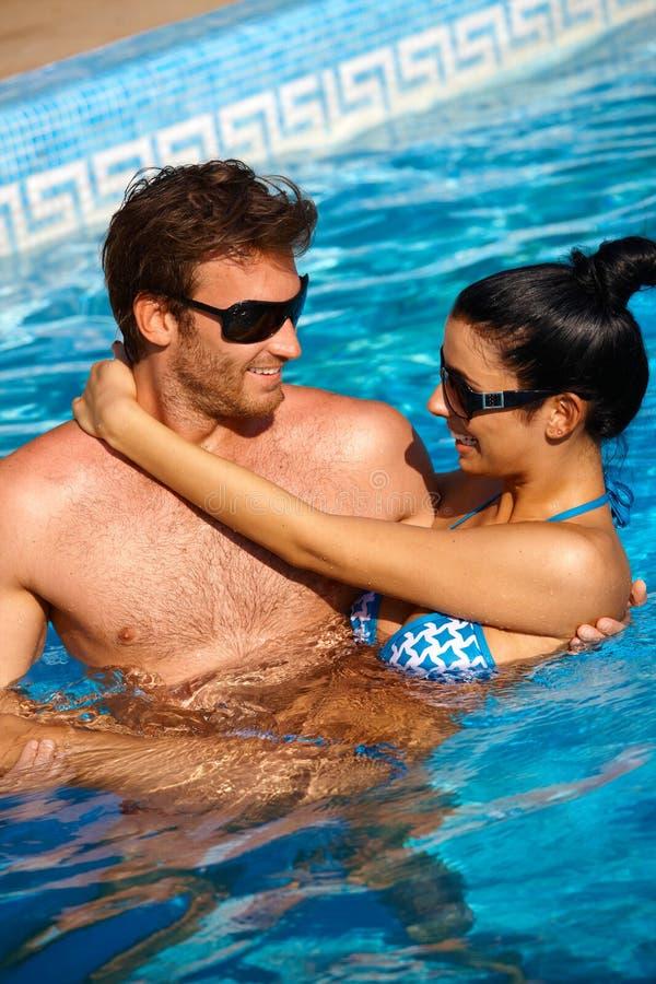 Pares Loving no sorriso da piscina imagem de stock