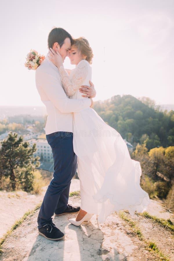 Pares loving novos atrativos de vestido branco vestindo do noivo e da noiva delicada que vibra no vento que está no CCB exterior  foto de stock royalty free