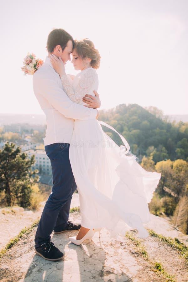 Pares loving novos atrativos de vestido branco vestindo do noivo e da noiva delicada que vibra no vento que está no CCB exterior  imagens de stock royalty free