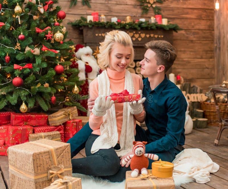Pares loving novos do Natal que abrem um presente junto imagem de stock