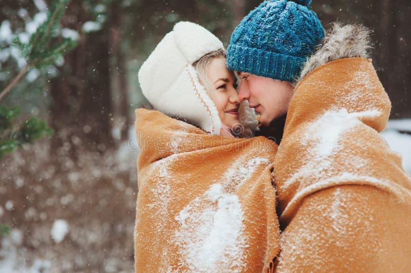 Pares loving novos felizes que andam na floresta nevado do inverno, coberta com o lenço e o abraço de tamanho grande fotos de stock royalty free