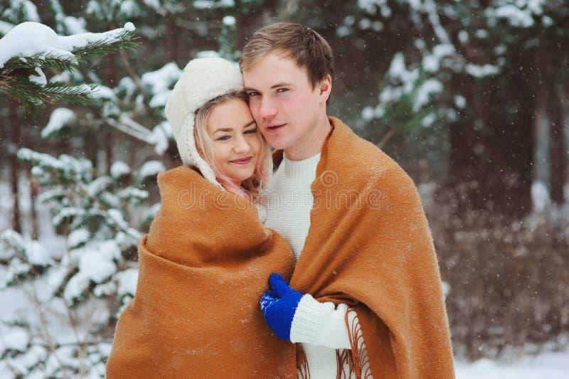 Pares loving novos felizes que andam na floresta nevado do inverno, coberta com o lenço e o abraço de tamanho grande imagem de stock