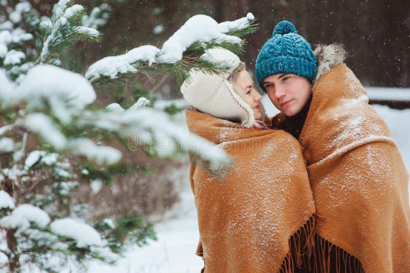 Pares loving novos felizes que andam na floresta nevado do inverno, coberta com o lenço e o abraço de tamanho grande fotografia de stock