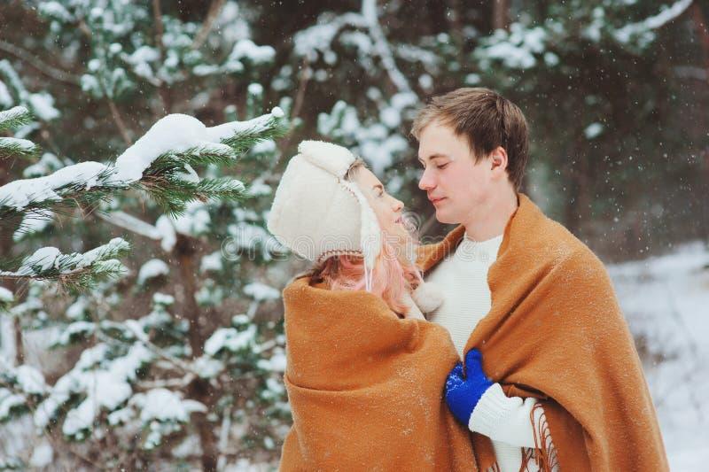 Pares loving novos felizes que andam na floresta nevado do inverno, coberta com o lenço e o abraço de tamanho grande imagens de stock
