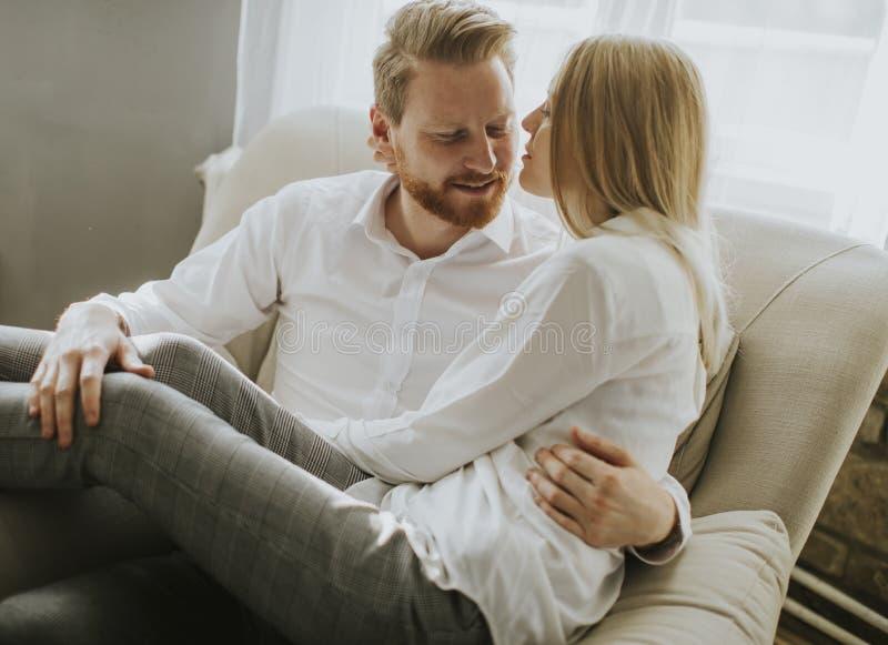 Pares loving novos no sofá imagem de stock royalty free