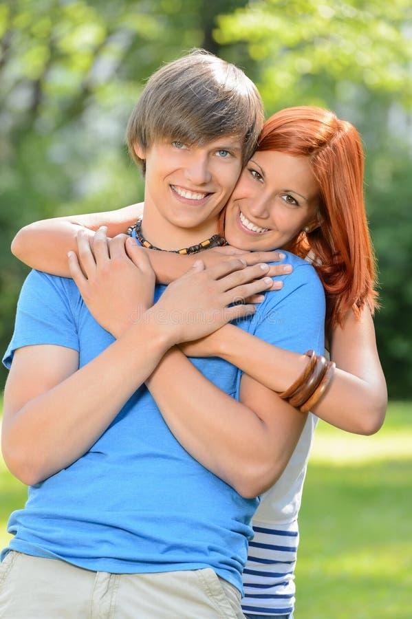 Pares loving novos que abraçam no parque ensolarado fotos de stock royalty free