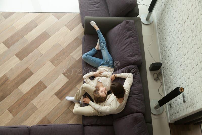 Pares loving novos que relaxam no sofá confortável junto, v superior imagens de stock royalty free