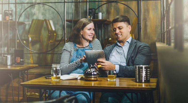 Pares loving novos que sentam-se no café na tabela e que usam o tablet pc A menina e o indivíduo usam o dispositivo digital, blog fotos de stock royalty free