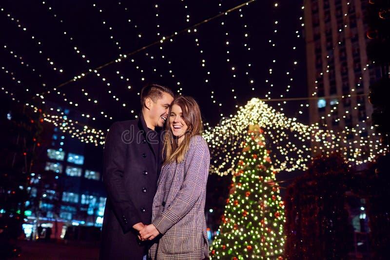Pares loving que abraçam o sorriso na noite no fundo do Ch imagens de stock