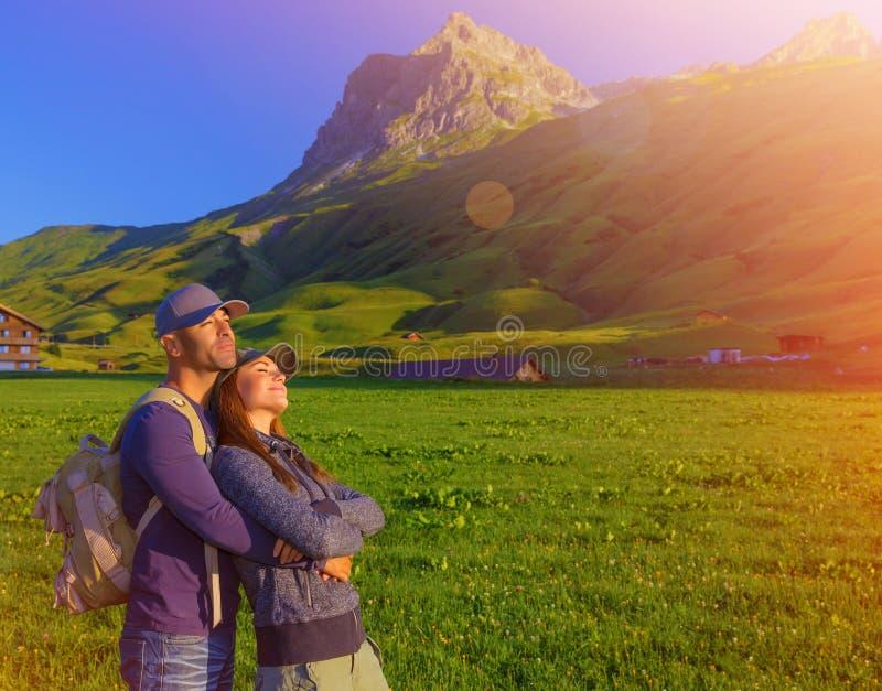 Pares loving que apreciam o por do sol nas montanhas foto de stock