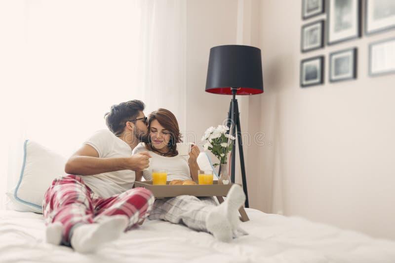 Pares loving que comem o café da manhã na cama foto de stock royalty free