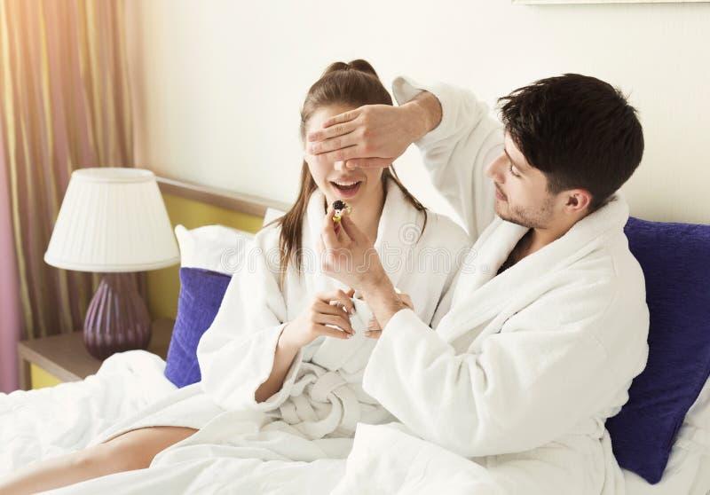 Pares loving que comem um café da manhã preguiçoso da manhã na cama do comfortabe imagens de stock