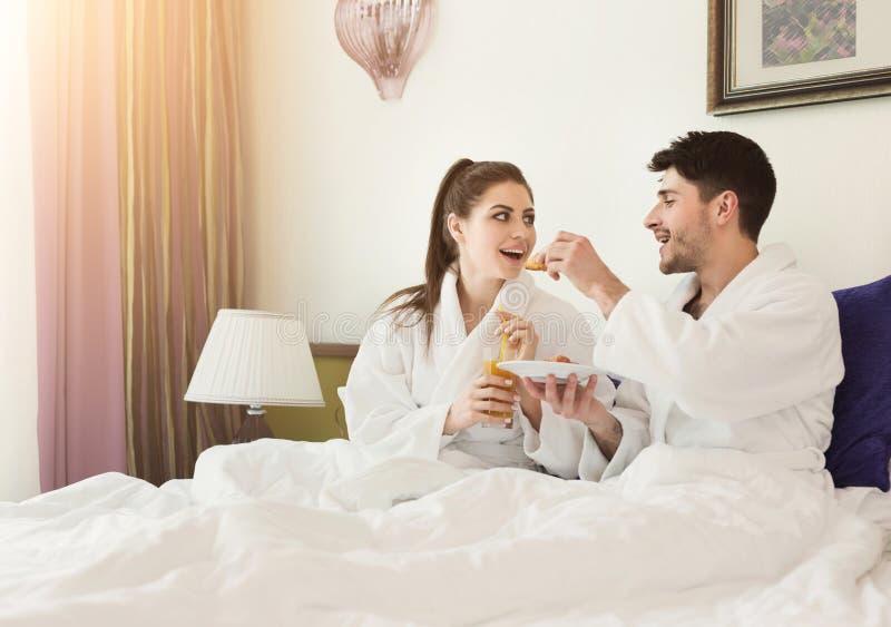 Pares loving que encontram-se na cama e que comem o café da manhã fotografia de stock royalty free