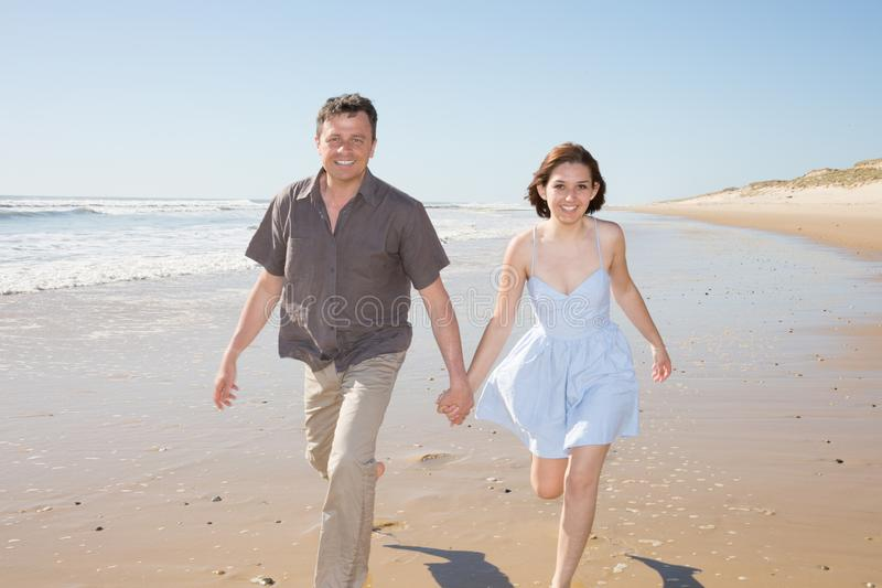 Pares loving que guardam as mãos e que andam na praia da areia com nascer do sol bonito no amor e na liberdade do feriado foto de stock