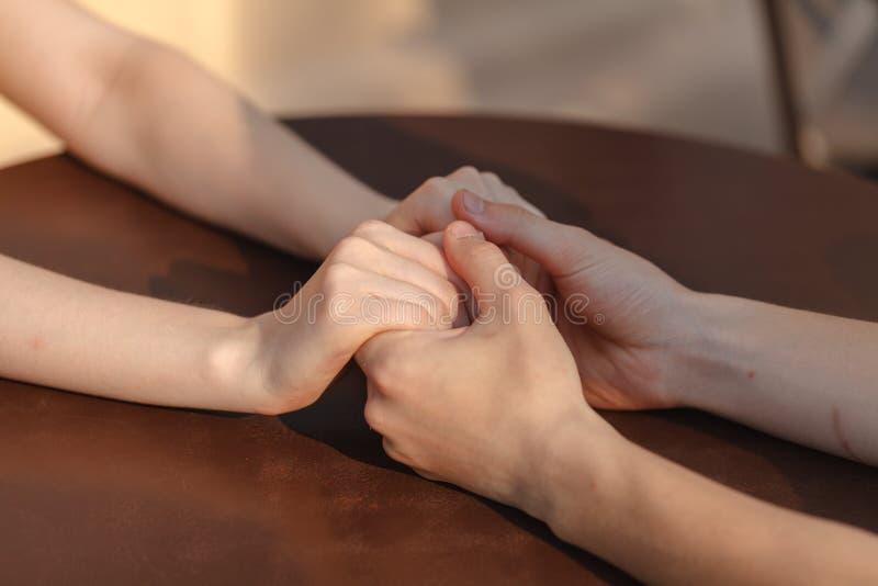 Pares loving que guardam as mãos na tabela no café fotografia de stock royalty free