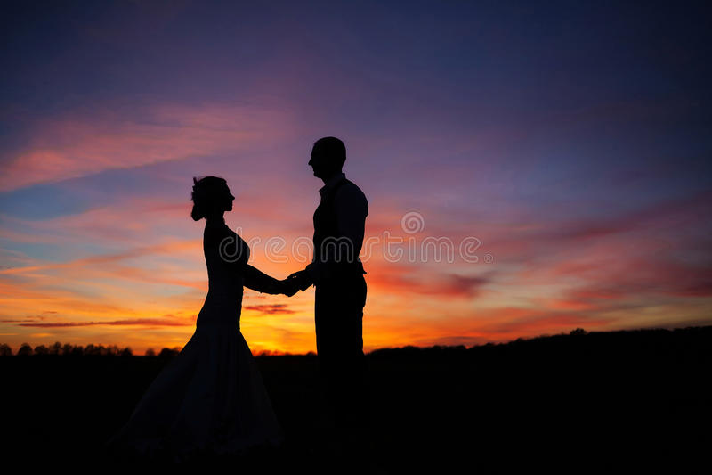 Pares loving que guardam as mãos no por do sol foto de stock royalty free