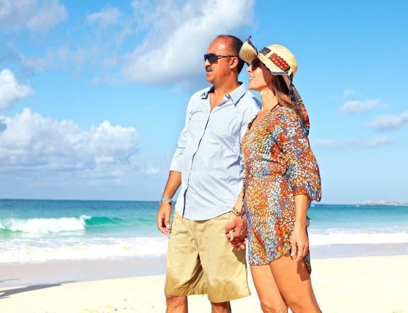 Pares loving que relaxam na praia imagens de stock royalty free